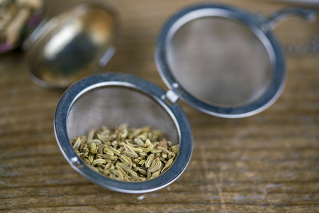 A close up of fennel seeds in a metal tea strainer on a rustic timber bench.