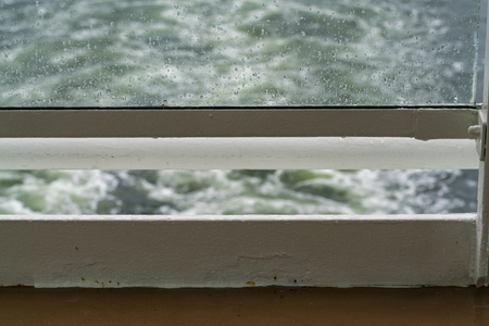 Close up of sea water spray on a glass ship railing, with the sea in the background.