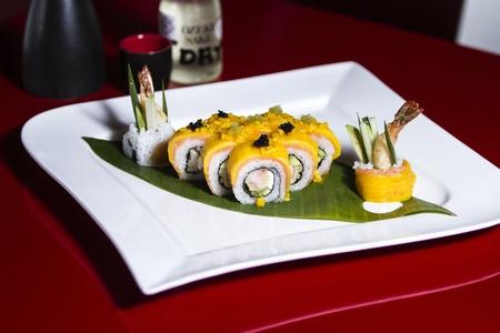 Banaan en zalm sushi roll met kaviaar toping en garnalen opzij