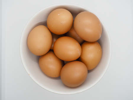 Many Chicken Brown Eggs in the white bowl with white background Stock Photo