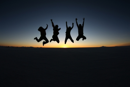 A group of happy young friends jumping outdoor photo