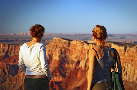 Two young women watching the sunset at the Grand Canyon 스톡 콘텐츠