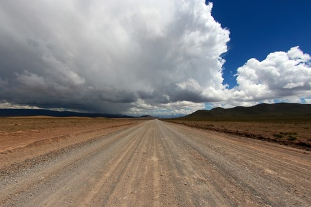 unpaved road: The lonely straight unpaved road in Andes, Argentina Stock Photo