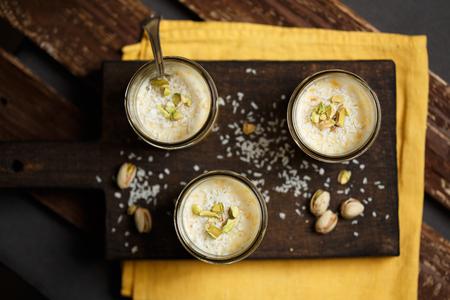 latte fresco: Panna cotta con mango, noce di cocco e pistacchi su un tagliere di legno