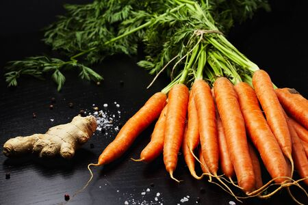 biology backgrounds: Bunch of fresh carrots with green leaves on wooden table