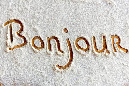bonjour: Bonjour word written in flour closeup. Stock Photo