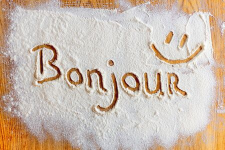 bonjour: Bonjour word written in flour closeup. Stock Photo