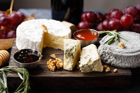 plato de comida: Placa de queso servido con vino, mermelada y miel de cerca