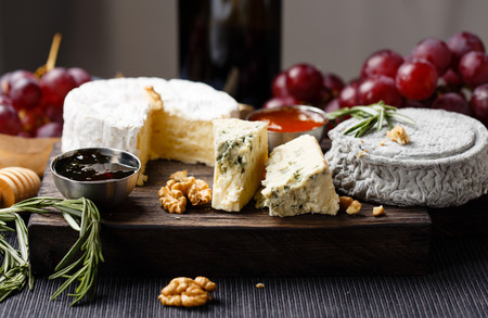 queso blanco: Cheese plate  served with wine, jam and honey close-up Foto de archivo