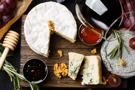 queso blanco: Cheese plate served with wine, jam and honey top view Foto de archivo