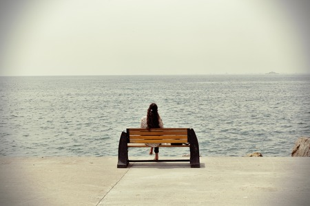 Lonely woman sitting at the sea coast