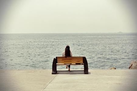 Mujer sola que se sienta en la costa del mar