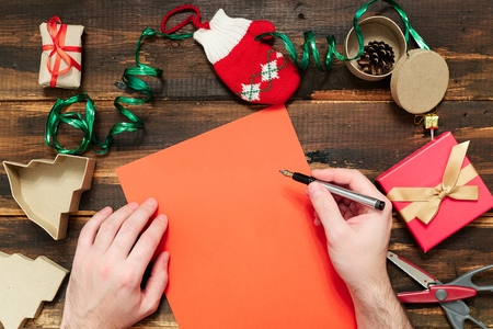 papier lettre: Christmas letter writing on red paper on wooden background with decorations Banque d'images