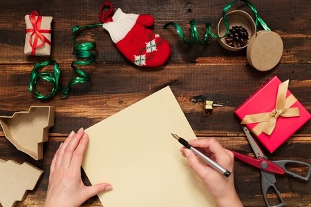 xmas crafts: Christmas letter writing on yellow paper on wooden background with decorations