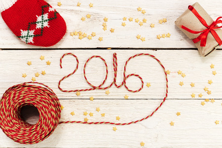 Happy New year 2016, numbers maden by wrapping thread of yarn on wooden background with Christmas decorations Stok Fotoğraf - 48973494