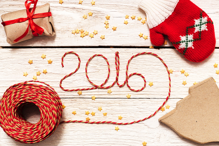 Happy New year 2016, numbers maden by wrapping thread of yarn on wooden background with Christmas decorations Stok Fotoğraf - 48973498