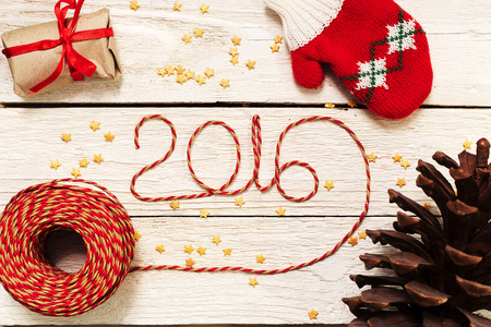 Happy New year 2016, numbers maden by wrapping thread of yarn on wooden background with Christmas decorations Stok Fotoğraf - 48973500