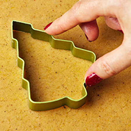 Female hand making christmas tree gingerbread cookies with metal cutter