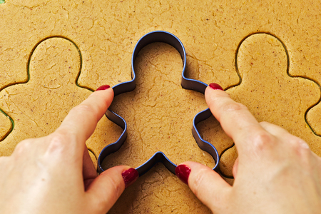 Female hand making christmas gingerbread men cookies with metal cutter 스톡 콘텐츠
