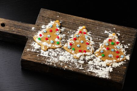 Christmas tree gingerbread cookie on wooden board stylish with powdered sugar 스톡 콘텐츠