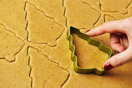 Female hand making christmas tree gingerbread cookies with metal cutter.