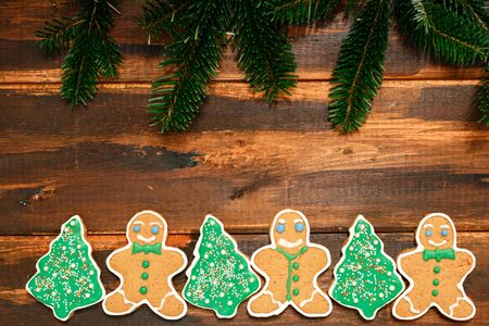 Gingerbread Christmas cookies with natural fir branch on the wooden background