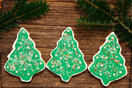 Gingerbread Christmas tree cookies with fir's branch on the wooden background
