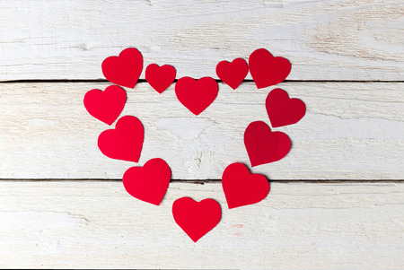 Red heart paper cut on white wooden background. Valentines day.