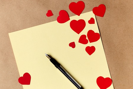 Valentines day letter writing on yellow paper with heart paper cut decoration