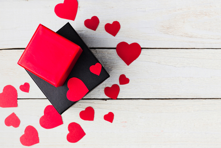 Gift boxes and heart paper cut on white wooden background. Valentines day.