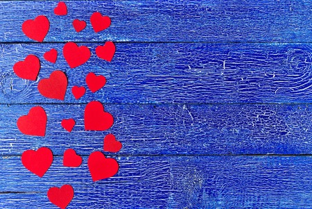 Red heart paper cut on blue wooden background. Valentines day.