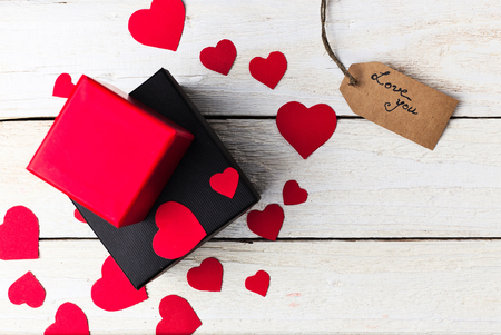 Gift boxes and heart paper cut with craft label and love confession on white wooden background. Valentines day.