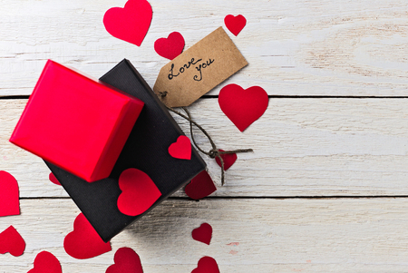 confession: Gift boxes and heart paper cut with craft label and love confession on white wooden background. Valentines day.