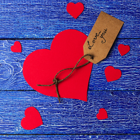 Red heart paper cut with craft label on blue wooden background. Square composition for Valentines day.