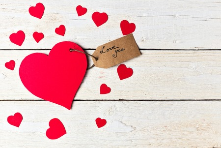 Red heart paper cut with craft label on white wooden background. Valentines day.