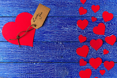 Red heart paper cut with craft label on blue wooden background. Valentines day.