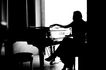 black and white woman silhouette sitting near grand piano