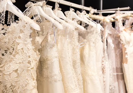 fancy dress: white wedding dresses hanging on shoulders and pegs