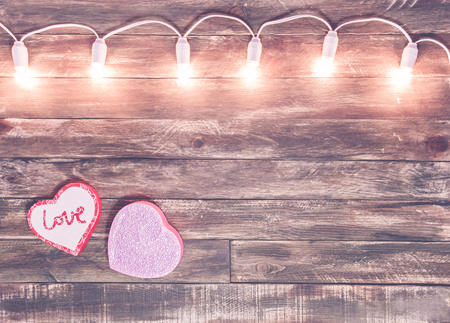 saint valentine wooden textured background with light garland