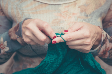 warm cloth: manicured woman hands knitting green cloth, warm vintage