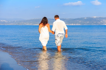 mid morning: Young couple walking along lonely beach at sunset Stock Photo