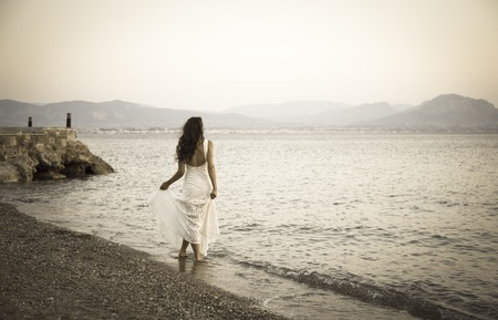 Girl standing on the beach with white dress retro photo
