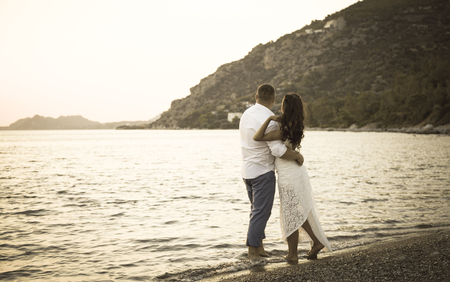 back view of happy young couple in white on the beach. Retro photo Imagens