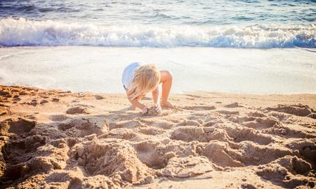kid play with sand on summer beach