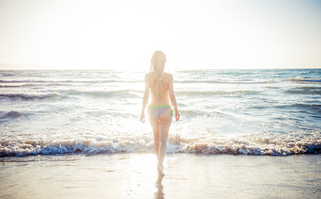 Young woman standing by blue sea and looking to horizon