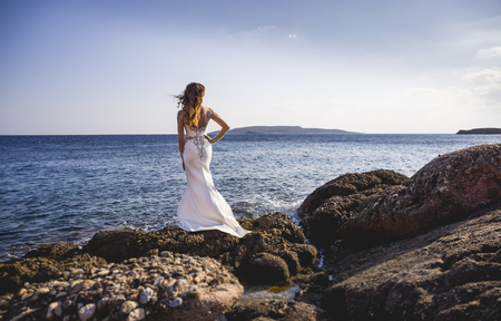 Bride standing on rocks on a sea shore and looking at water Imagens