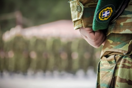 officers hand holding beret during oath in Greek army