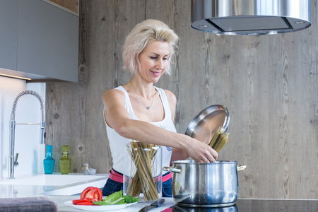 young blonde woman cooking in modern kitchen Imagens - 123859844