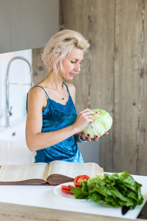 young blonde woman cooking in modern kitchen Imagens - 123859873