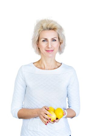 portrait of young blond woman holding lemons on white background
